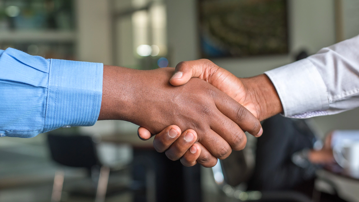 Recruiting image: Showing collaboration via two individuals shaking hands.