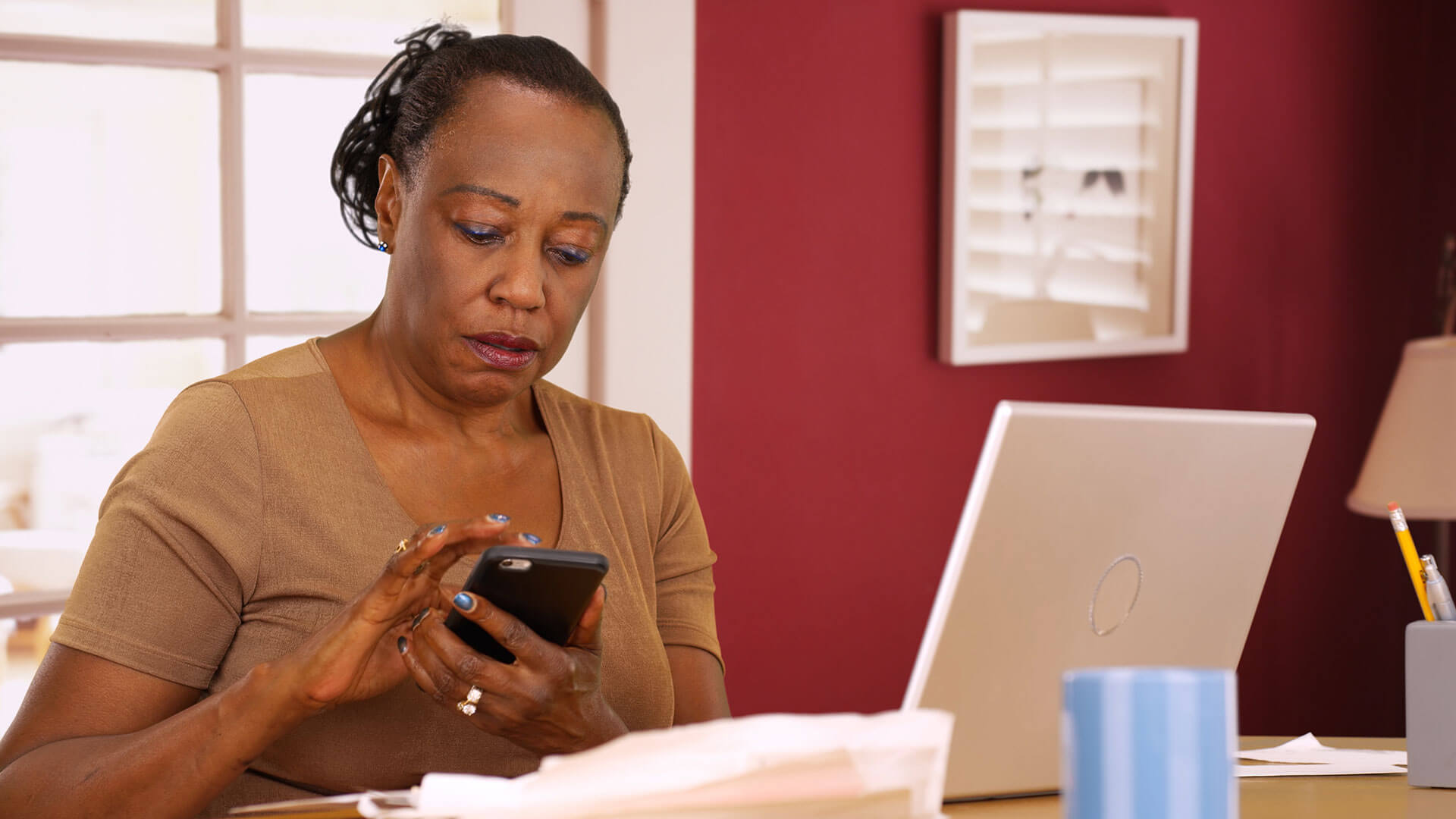 A women participating in a menopause study by using her smartphone while sitting at a desk.