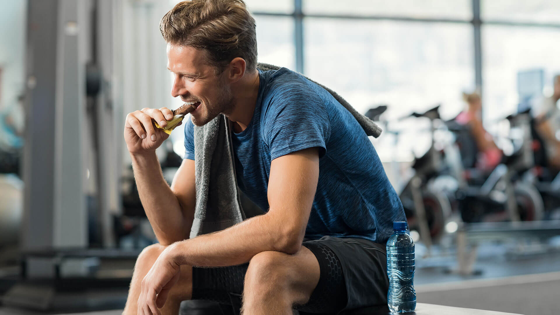 A man consuming a fiber snack bar inside of a gym, post-workout.