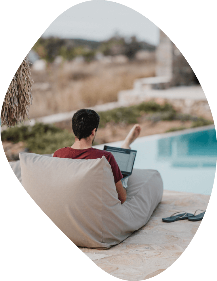 A barefoot man sitting pool-side while using his laptop.