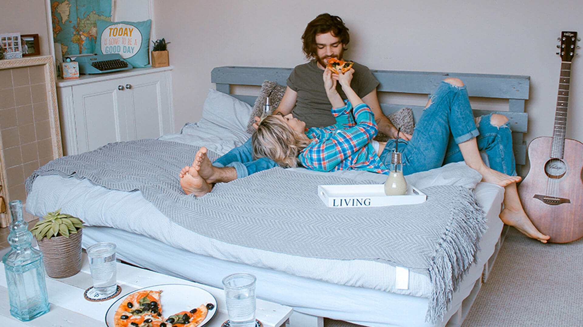 A couple laying on a bed, eating pizza.