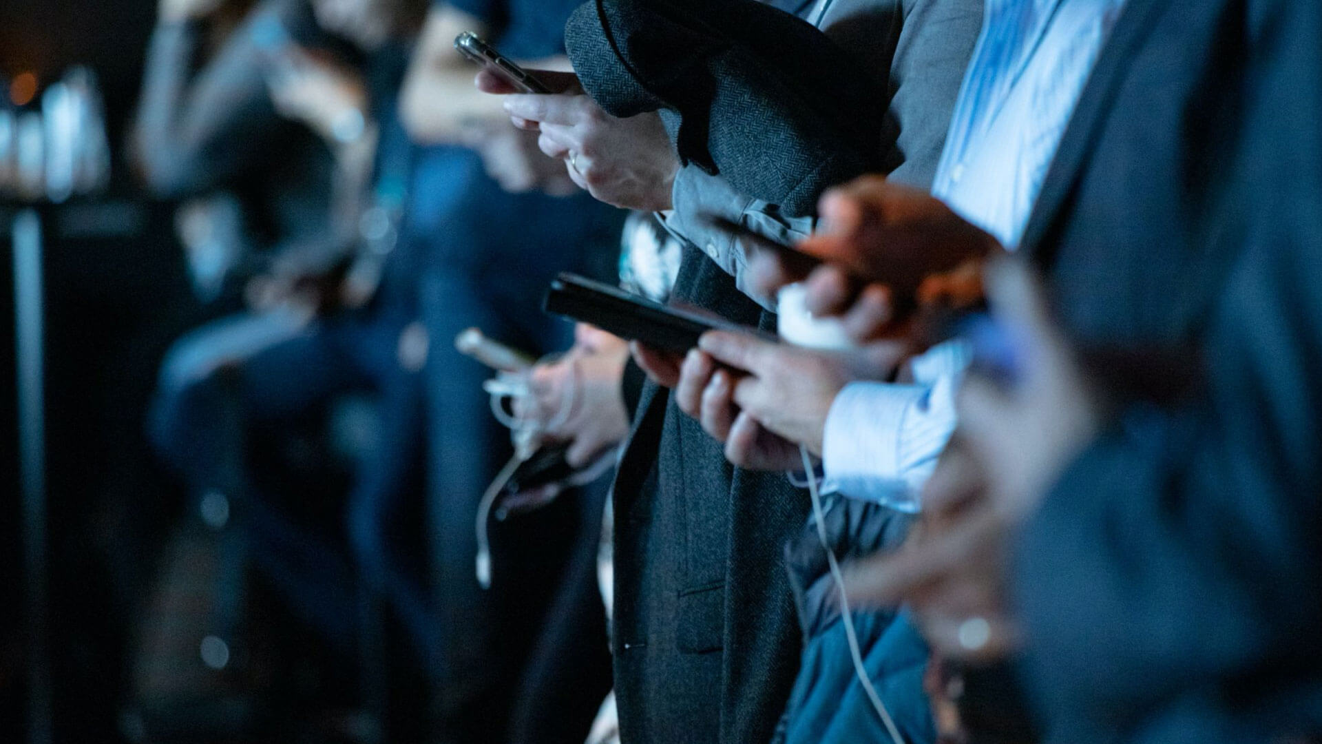 A line of professionally-dressed individuals standing side-by-side, all using smartphones.