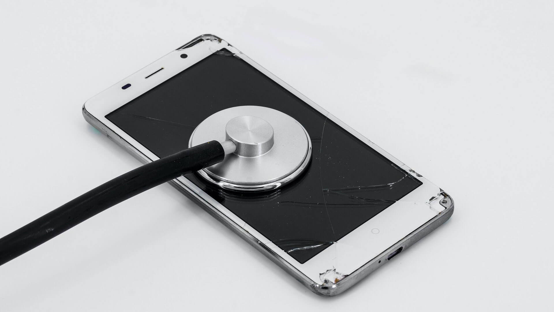 A smartphone with a cracked screen, stethoscope laying on top of phone.