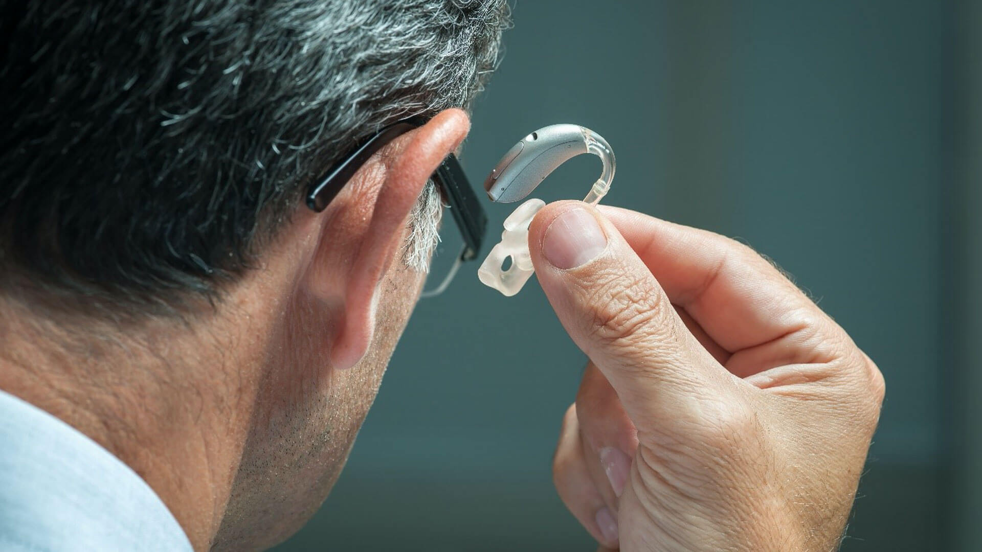 A man with medical device that appears as as a hearing aid.