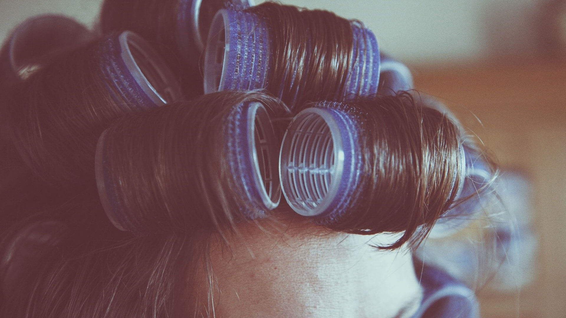 Hair rollers in a woman's hair.