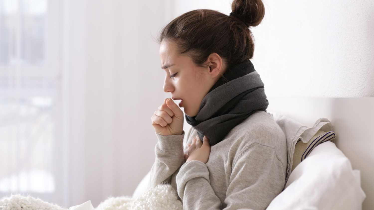 A women coughing while sitting up in bed.