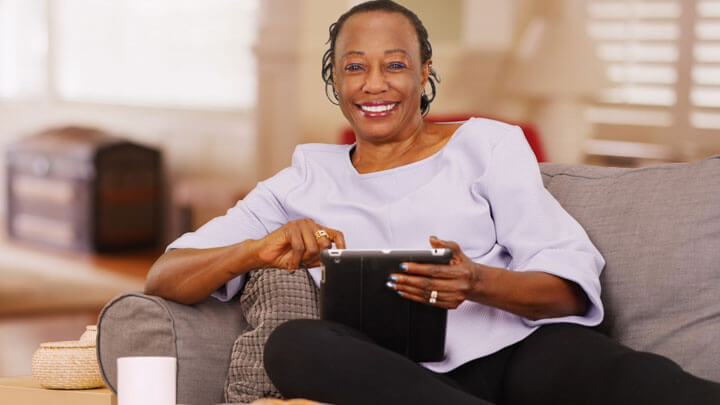 A woman, smiling at camera, sitting on couch at home with tablet in hand.