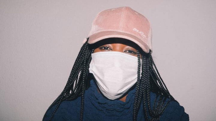 A woman with a pink hat and white face mask, staring into camera.