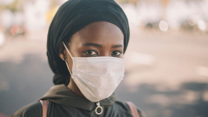 A woman wearing a face mask, looking into camera.