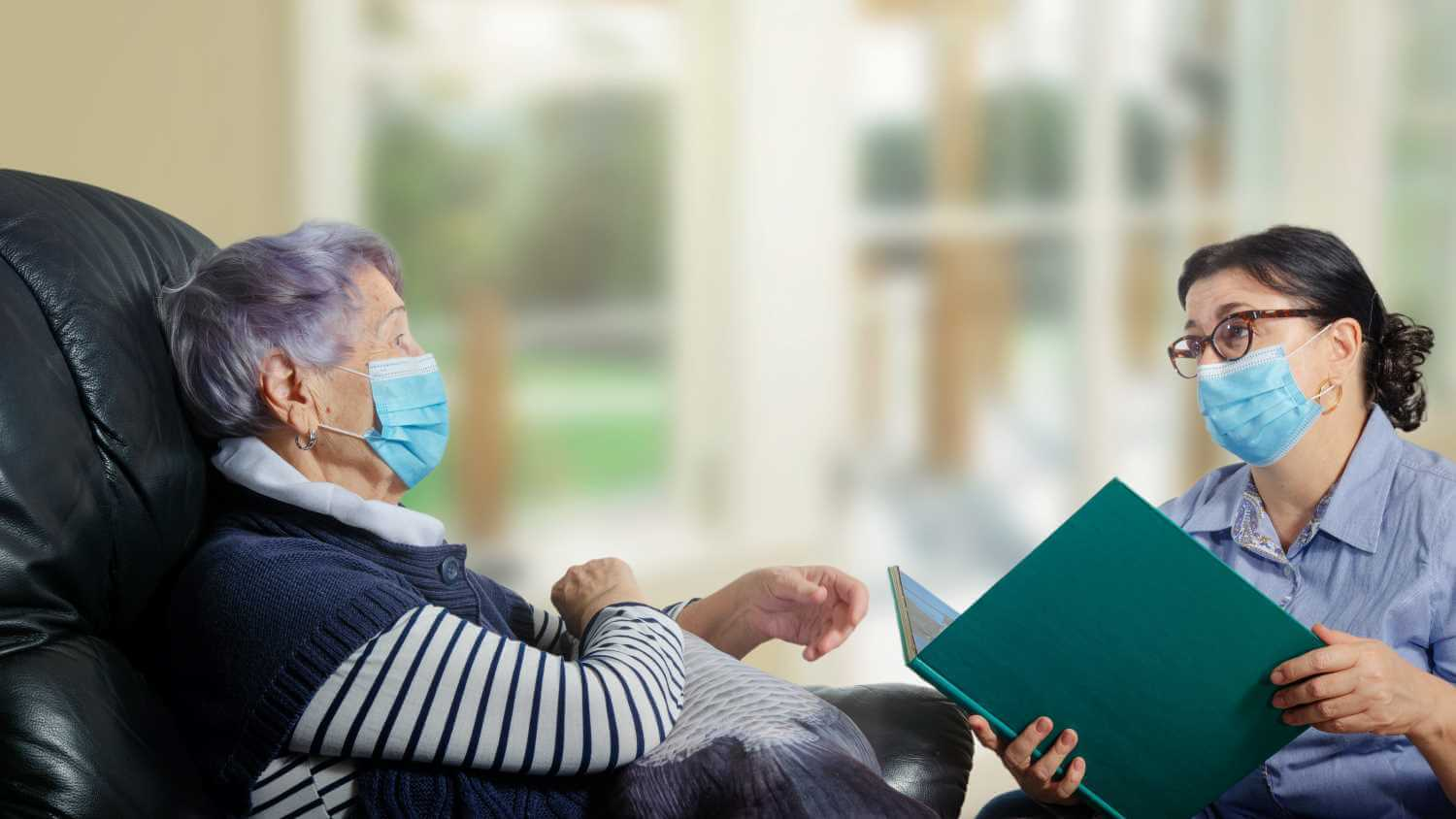 A patient and healthcare professional, both wearing masks, holding conversation.