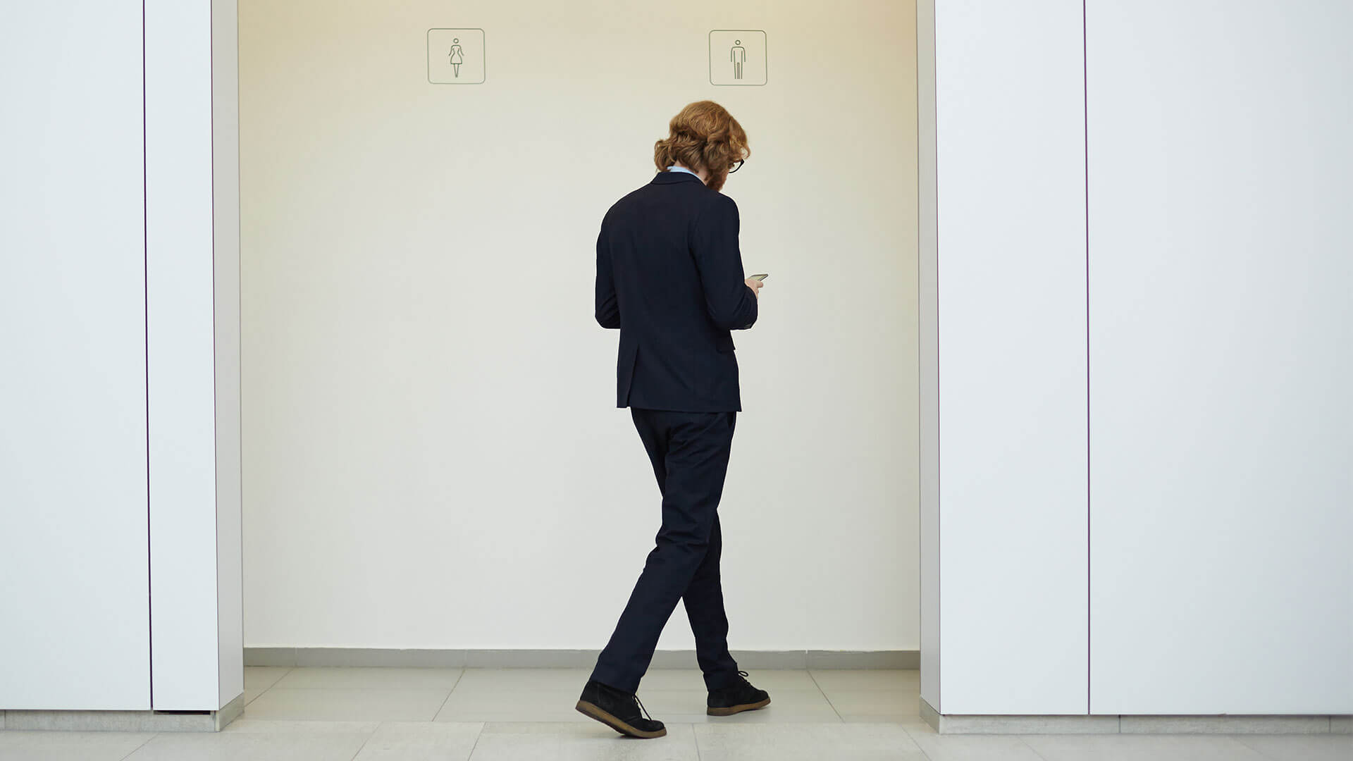 A man, walking with his head down, looking at his phone, into the mens restroom.