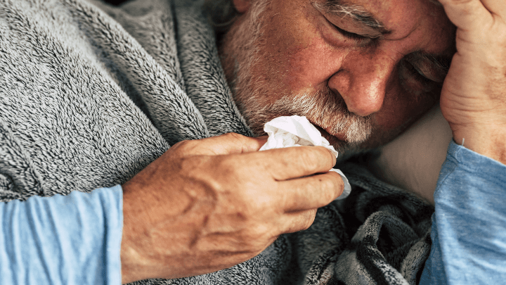 An elderly gentleman with a cold, using a tissue to wipe mouth.