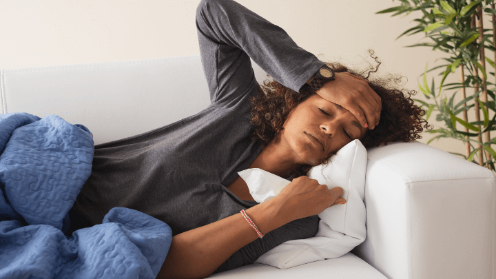 A woman laying on the couch, suffering from flu-like symptoms.