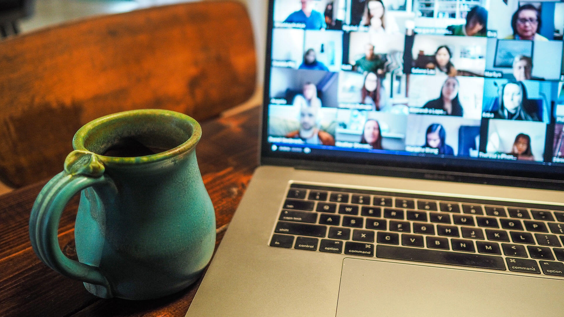 A mug next to a laptop with users in a group chat.