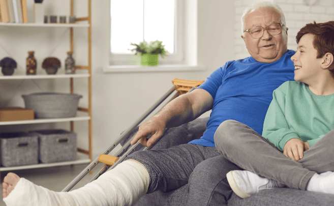 A grandpa sitting on the couch with his grandson, recovering from what appears to be a leg injury (cast on leg).