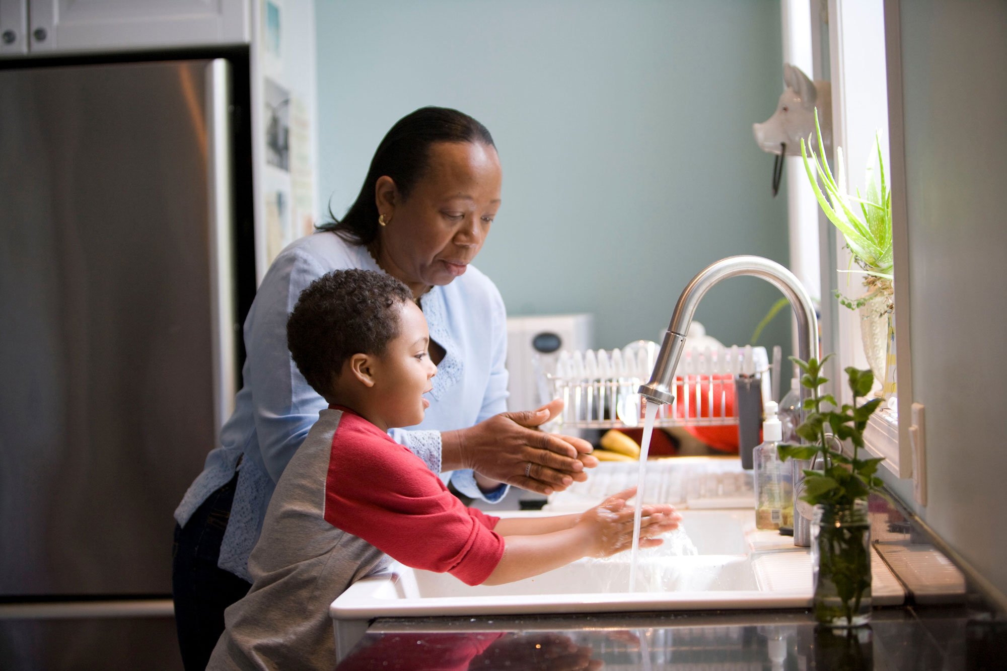 Adult and child washing hands at sink
