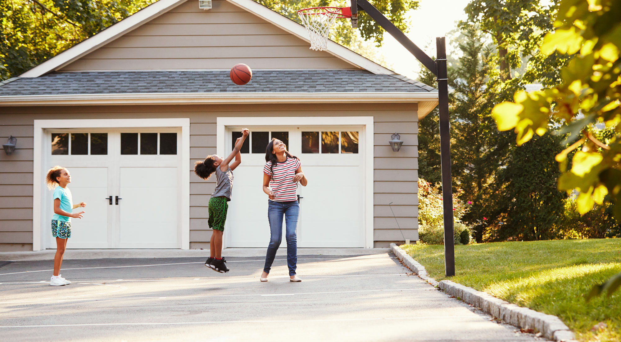 Kids playing basketball in driveway in suburbs