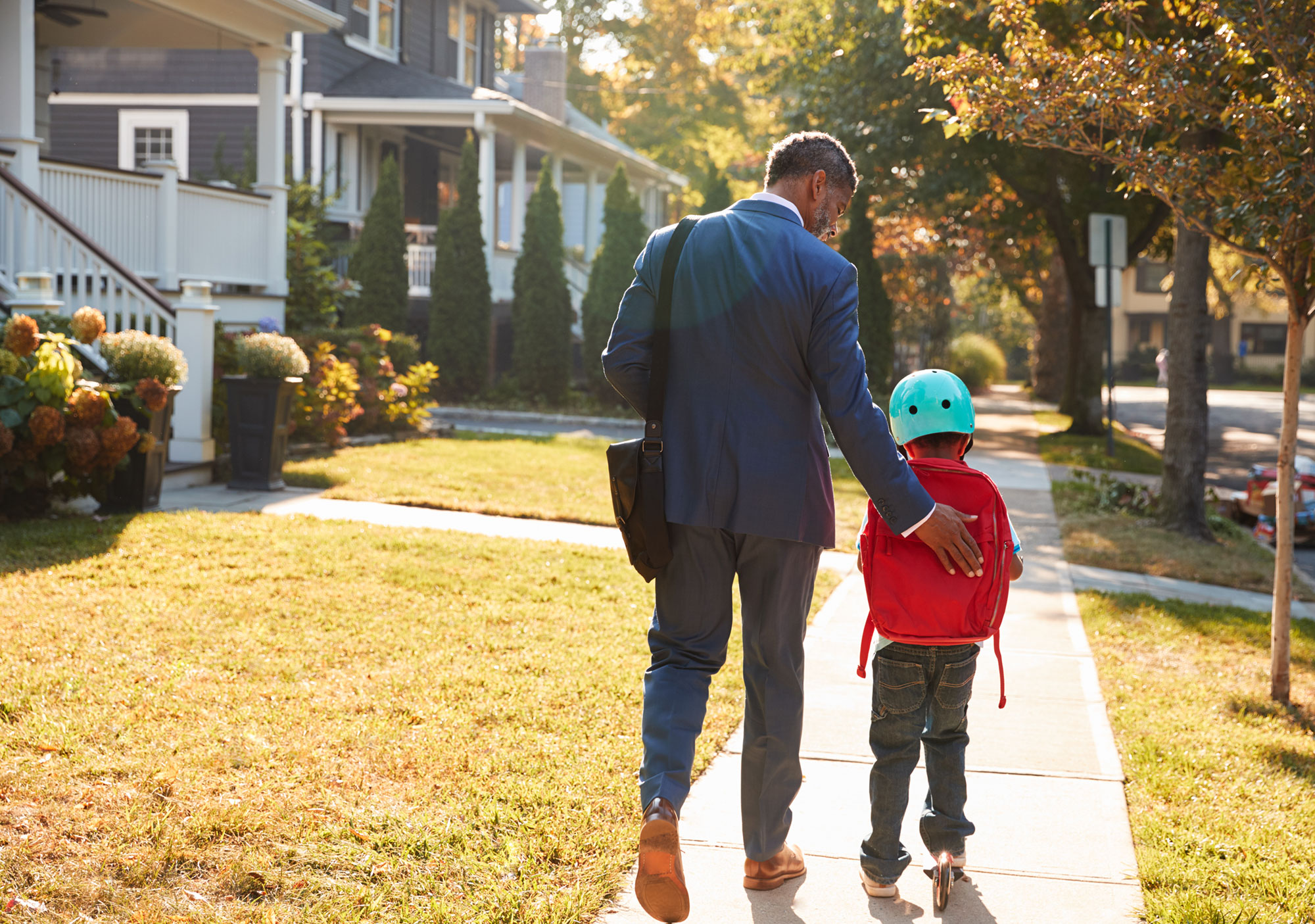 Father walking with son on sidewalk