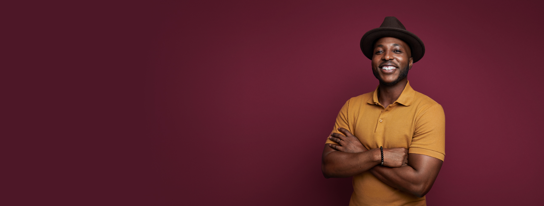 Smiling person on maroon colored background with mustard colored shirt and brown hat.