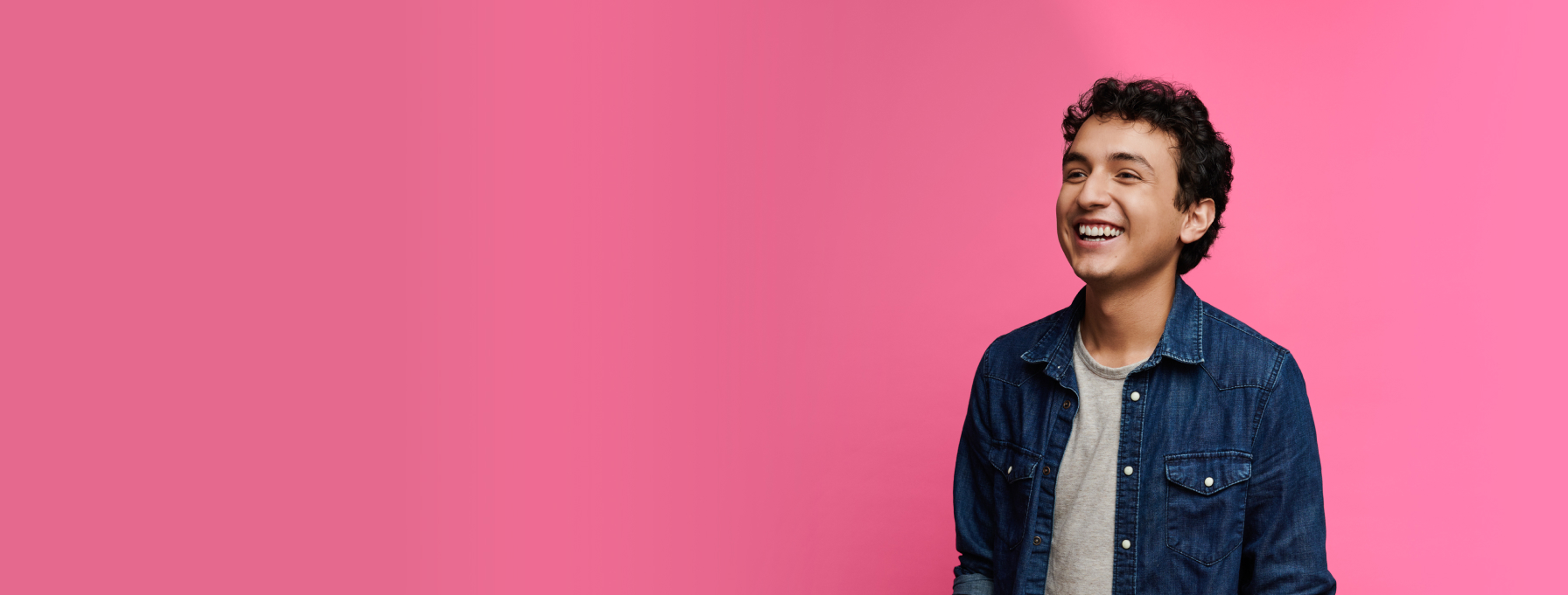 Smiling person on pink background.