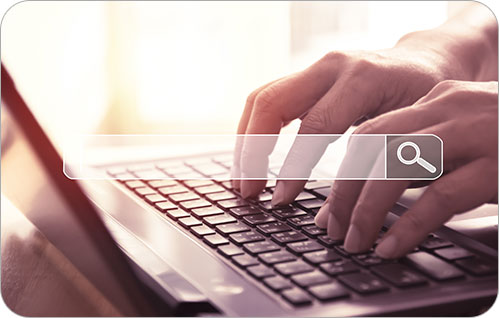 Closeup of someone typing on a laptop with a search bar graphic overlayed.