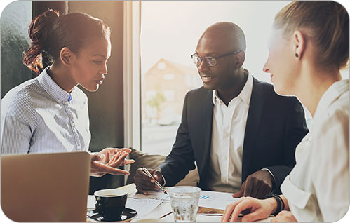 Three people sit around a coffee table and discuss business.