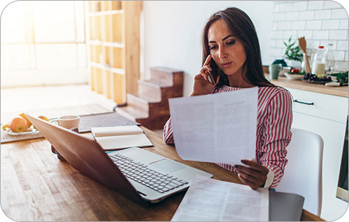 Uma mulher se senta à mesa na cozinha, olhando para um pedaço de papel enquanto fala ao telefone.