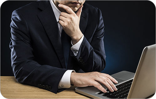A man in a suit at a desk looks at his laptop computer screen while holding his chin in contemplation.