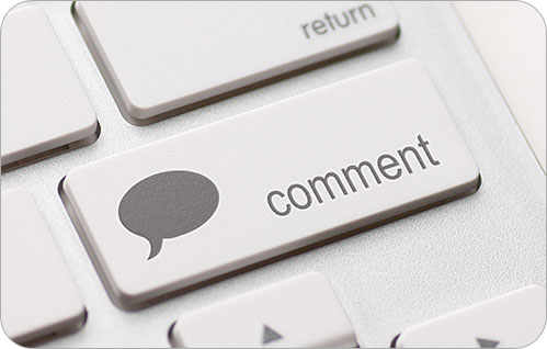 Extreme closeup of a shift key with the text Comment on it and a chat bubble.
