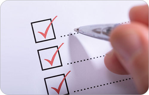 Extreme closeup of three checkboxes and a hand holding a pen.