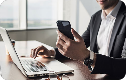 A man smiles while sitting at a desk smiling and holding a cellphone.