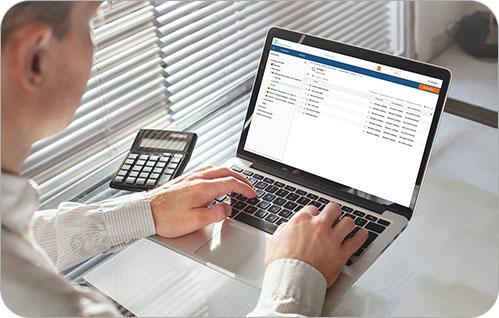 A man types on a laptop computer.