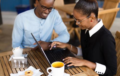 Duas pessoas tomam café enquanto olham para a tela de um laptop.