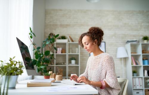 Uma mulher está sentada em uma mesa, olhando para o teclado em que está digitando.