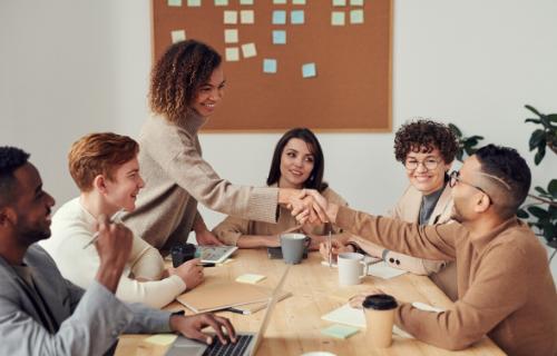 Um grupo de pessoas está sentado ao redor de uma mesa de conferência com duas pessoas apertando as mãos enquanto outras assistem.