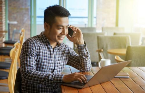 Um homem sorri enquanto fala ao telefone e digita em um laptop.