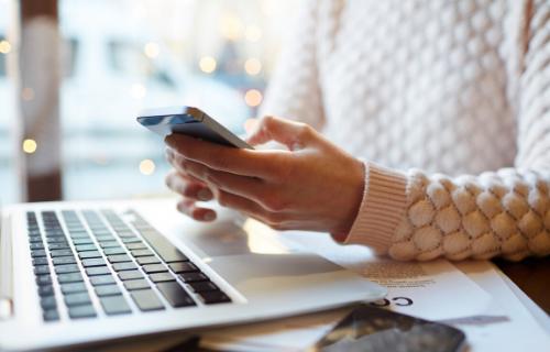 Close de uma mulher segurando um celular sobre um laptop.