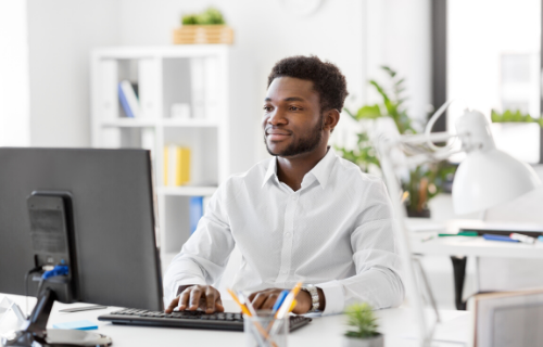 Vista frontal de um homem sorrindo enquanto olha para a tela do computador.