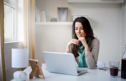 Uma mulher sorri enquanto olha para a tela do computador.