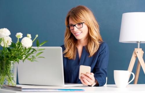 Uma mulher sorri enquanto olha para a tela de seu laptop e segura um celular.