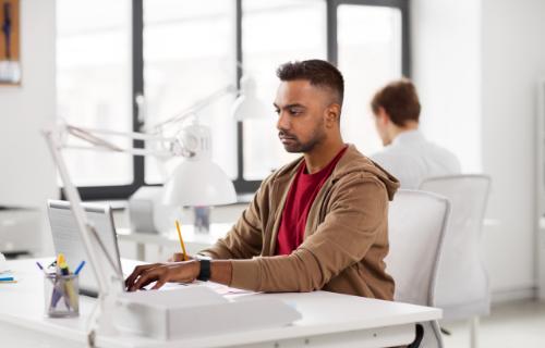 Vista lateral de um homem digitando e olhando para a tela de um computador laptop.