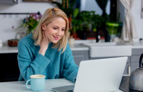 Uma mulher sorri com café ao lado dela enquanto olha para a tela de seu laptop.