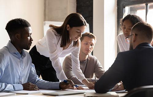 Um grupo de empresários fica em volta de uma mesa e analisa documentos.