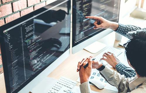 Duas pessoas estão sentadas em uma mesa com dois monitores Mac e apontam para um código na tela.