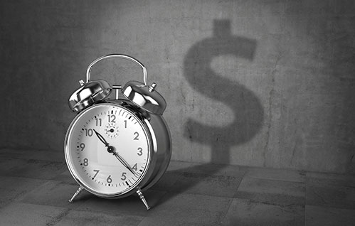 An analog alarm clock sits on a concrete background with a dollar sign as its shadow.
