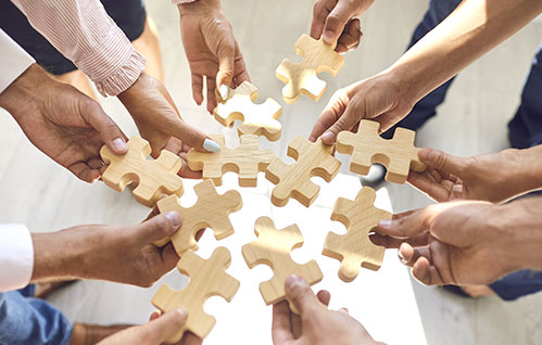 Closeup of a group of people standing in a circle holding puzzle pieces.