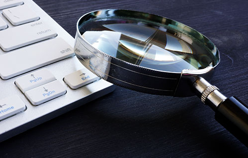 Closeup of a magnifying glass next to a keyboard.