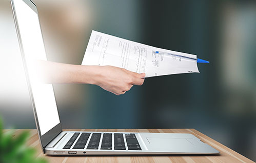 An arm extends outside of a laptop computer screen holding a document with a pen attached.