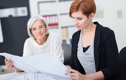 Two women sit around a desk and review a big paper.