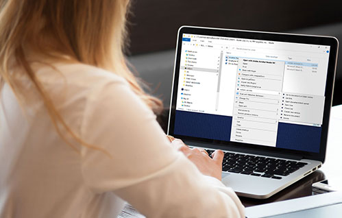 Uma mulher está sentada em um laptop e olha para o produto NetDocuments ndSync.